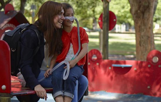 Mutter auf dem Spielplatz mit beatmetem Kind