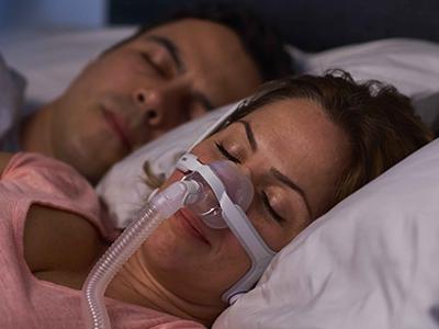 Schlafapnoe-Patientin trägt ResMed Nasenmaske