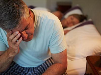 Mann leidet unter Kopfschmerzen und Morgenmüdigkeit aufgrund von Schlafapnoe